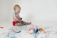Baby boy playing with homemade fingerpaints. A baby boy in a reusable nappy makes a mess with paint Royalty Free Stock Image