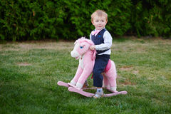 Baby boy playing with horse on playground in park Stock Photos