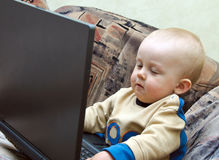 Baby boy playing with laptop stock photo