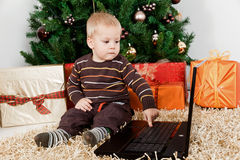 Baby boy playing with a laptop at christmas Stock Images
