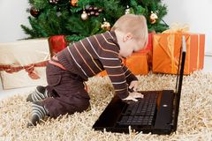 Baby boy playing with a laptop at christmas Royalty Free Stock Photos