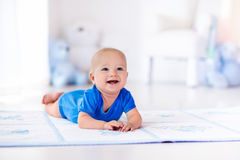 Baby boy playing and learning to crawl Stock Photo