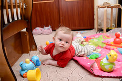 A baby boy is playing and looking at the camera Stock Photos