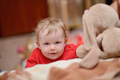 A baby boy is playing and looking at the camera Royalty Free Stock Images