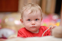 A baby boy is playing and looking at the camera Stock Image