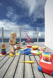 Baby Boy Playing With Lots Of Toys On Porch. Full length of happy baby boy playing with lots of toys on wooden porch Stock Photo
