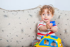 Baby boy playing. 11 months old baby boy portrait playing with a toy car Stock Image