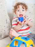Baby boy playing. 11 months old baby boy portrait playing with a toy car Royalty Free Stock Photography