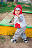 Baby boy playing near sandbox on the playground Stock Image
