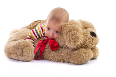 Baby boy playing over plush dog Royalty Free Stock Image