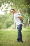 Baby boy playing in the park with dad. Little boy playing in the park with dad royalty free stock photography