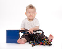 Baby boy playing with pc power supply on white Royalty Free Stock Image