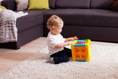 Baby boy playing with plastic sorter toy. Sitting on a floor stock images