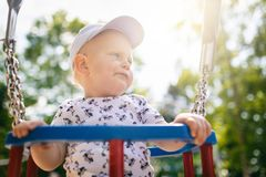 Baby boy playing in playground having fun. Baby boy playing in playground area. Portrait of smiling toddler looking away with happy face, having fun. Swaying on Stock Photos