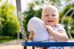Baby boy playing in playground having fun. Baby boy playing in playground area. Portrait of smiling toddler looking at camera with happy face, having fun Stock Photo
