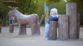 Baby boy playing on the playground in the park. He stands near the tree stumps. Against the background of a wooden deer. stock video