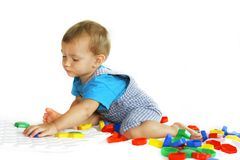 Baby boy playing with puzzle. Baby boy playing with colorful puzzle over white Royalty Free Stock Images
