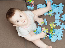 Baby boy playing with puzzle pieces on sofa in the living room at home Royalty Free Stock Images
