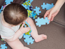 Baby boy playing with puzzle pieces on sofa in the living room at home Stock Images