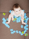 Baby boy playing with puzzle pieces on sofa in the living room at home Royalty Free Stock Image
