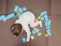 Baby boy playing with puzzle pieces on sofa in the living room at home Royalty Free Stock Photo