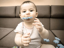 Baby boy playing with puzzle pieces on sofa in the living room at home royalty free stock photography