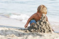 Baby boy playing with sand. On beach Stock Photos