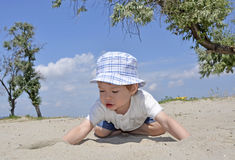 Baby boy playing in sand on beach. Cute active baby boy playing in sand on beach Stock Photography