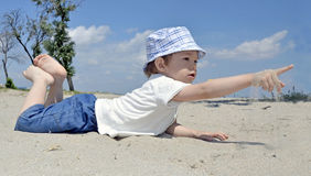Baby boy playing in sand on beach. Cute active baby boy playing in sand on beach Royalty Free Stock Photos