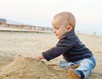 Baby boy playing in sand Stock Images