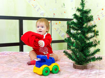 Baby boy playing with Santa Claus hat at home. Near Christmas tree and toy train Stock Photos