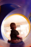 Baby boy playing on slide. Baby boy descending enclosed slide in play area, seen from behind Stock Photos