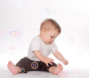 Baby boy playing with soap bubbles on white Stock Photo