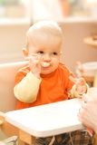 Baby boy playing with spoon Stock Photo