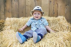 The Baby boy is playing on a straw bale. Baby boy is playing on a straw bale Royalty Free Stock Image