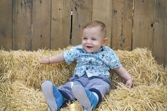 The Baby boy is playing on a straw bale. Baby boy is playing on a straw bale Stock Photo