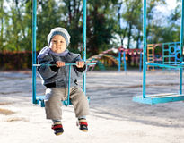 Baby boy playing on swing in autumn park Stock Images