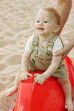Baby boy playing / swinging on beach Stock Photography