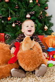 Baby boy playing with a teddy bear at christmas Stock Photo