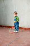 Baby boy playing tennis. Little baby boy playing with tennis bat and tennis ball, giving a cute, serious look at the camera Royalty Free Stock Image