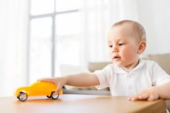 Baby boy playing with toy car at home. Childhood and people concept - baby boy playing with toy car at home royalty free stock image