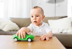 Baby boy playing with toy car at home. Childhood and people concept - baby boy playing with toy car at home royalty free stock images