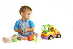 Baby boy playing with toy-truck. Over white royalty free stock image