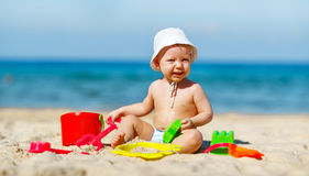 Baby boy playing with toys and sand on beach Stock Image