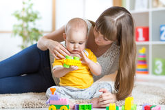 Baby boy playing toys together mother Stock Images