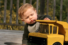 Baby Boy Playing with Truck. A baby boy playing with his yellow truck. Focus on the truck Royalty Free Stock Image