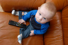 Baby boy playing with TV remote Stock Image