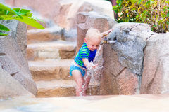 Baby boy playing with water tap outdoors Stock Images
