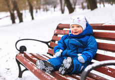 Baby boy playing in winter park. Happy family enjoy snow and winter on holidays Royalty Free Stock Images
