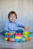 Baby boy, playing with wooden train toy Stock Photos